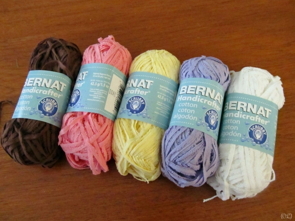 Bernat Handicrafter Scrubby yarn in Brown, Pink, Yellow, Purple, and White.